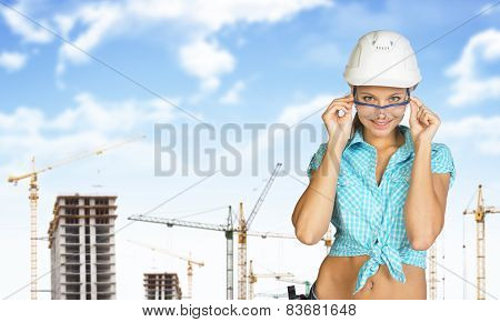 Woman in hard hat adjusting protective glasses