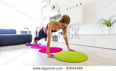 Young woman doing pushups in her living room.