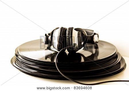 Headphones lying on the stack of vinyl records. Music concept.