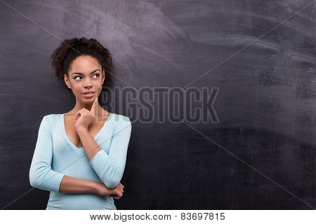 Young afro-american woman is near chalkboard