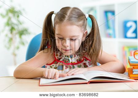 smiling little student girl reading book