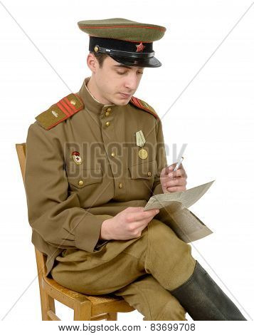 A Young Soviet Officer Sitting In A Chair Read A Newpaper