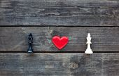picture of envy  - red heart between two chess kingd on rustic wood - JPG