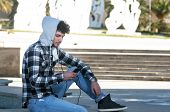 pic of hoodie  - young stylish bearded man in hoodie checkered shirt listening music in the city - JPG