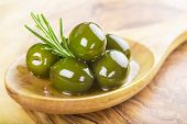stock photo of kalamata olives  - wooden spoon with green olives olive oil and some fresh rosemary on a cutting board - JPG