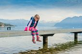 stock photo of legs air  - Adorable little girl sitting on a pier by the lake and swinging legs in the air - JPG