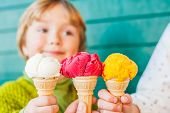 pic of corn  - Three corn of ice cream holding by hands of mother and two kids - JPG