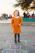 stock photo of hopscotch  - Cute little girl playing hopscotch on the street