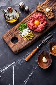 stock photo of tartar  - Beef tartare with pickled cucumber and fresh onions on dark marble background - JPG