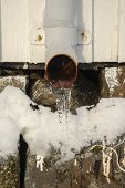 picture of waterspout  - Icicles Hanging From Frozen Iron Drainpipe at spring - JPG