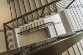 stock photo of upstairs  - staircase with wooden rail in a modern building - JPG