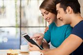 stock photo of heterosexual couple  - Side view of cheerful young loving couple sitting at the restaurant and using digital tablet - JPG