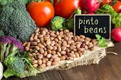 picture of pinto bean  - Pinto beans and vegatables on the old wooden table - JPG