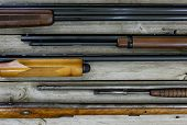 pic of gun shot  - Display of five guns lined up horizontal on wooden background - JPG