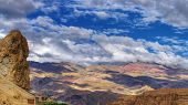 stock photo of jammu kashmir  - Rocky landscape of with ice peaks and blue cloudy sky in background blue sky with fluffy white clouds Ladakh Jammu and Kashmir India - JPG