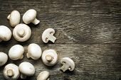 stock photo of champignons  - Fresh mushrooms champignons on wooden background close up - JPG