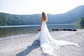 stock photo of long beach  - Beautiful bride trashing her white long dress and retinue at the lake beach watching the view - JPG
