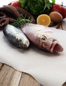 stock photo of sucker-fish  - Fresh fish and vegetables on wooden table  - JPG