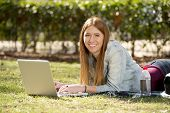foto of exams  - young beautiful student girl lying on park grass with computer laptop on rug studying happy preparing exam or surfing on internet in technology and education concept - JPG