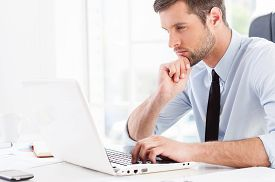 picture of thoughtfulness  - Side view of thoughtful young man in formalwear looking at laptop and holding hand on chin while sitting at his working place - JPG