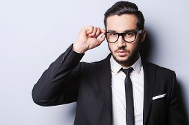 picture of shot glasses  - Portrait of handsome young man in formalwear adjusting his glasses while standing against grey background - JPG