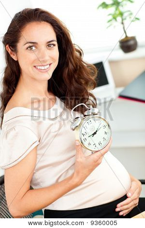 Radiant Pregnant Businesswoman Holding An Alarm Clock And Sitting At Her Desk