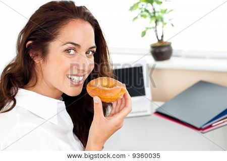 Happy Hispanic Businesswoman Eating A Doughnut