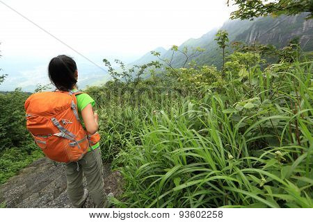 young woman backpacker hiking on mountian stairs