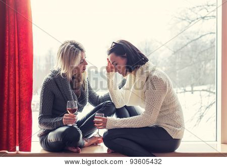 Two female friends talking while sitting at home