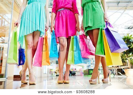 Group of shoppers in bright dresses holding paperbags