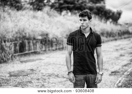 Young man in jeans and black t-shirt walking along rural road