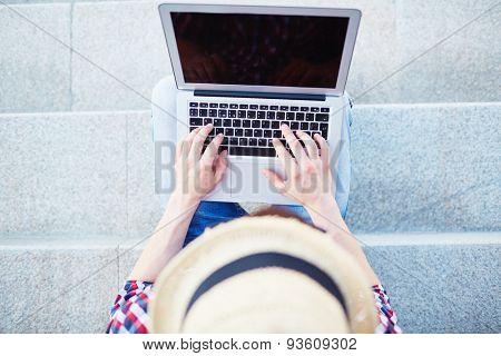 Modern guy typing on laptop outdoors