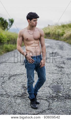 Shirtless muscular young man walking on rural road