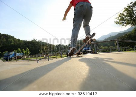 skateboarder legs doing a ollie at skatepark