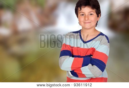 Casual young boy with arms crossed on a unfocused background