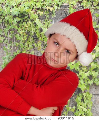 Angry boy dressed in red with christmas hat and plants background