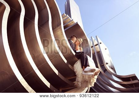 Bride And Groom Sitting On Architectural Metallic Piece