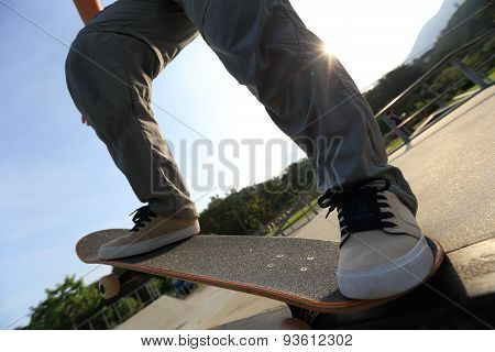 closuep of skateboarder legs riding skateboard at skatepark