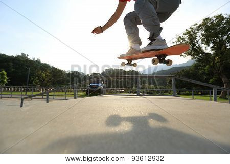 closeup of skateboarder legs doing a ollie at skatepark