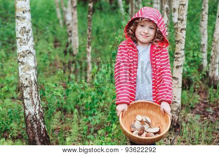 cute child girl gathering wild edible mushrooms in the forest