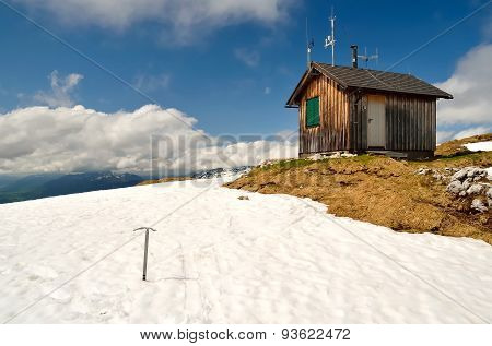 Ice axe stuck in the snow next to wooden hut in mountains.