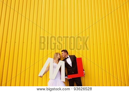 Bride And Groom Posing Against A Yellow Wall, Holding L And M Letters