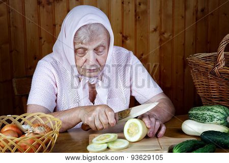 The Old Woman Cuts  Vegetable Narrow On A Table