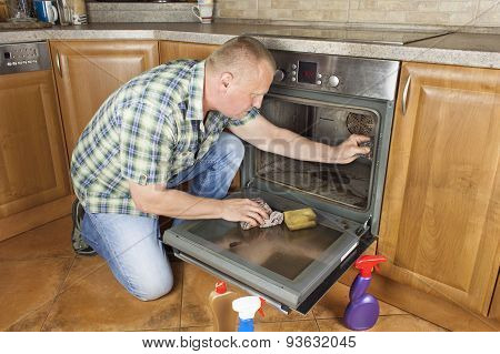 Man kneels on the floor in the kitchen and cleans the oven.
