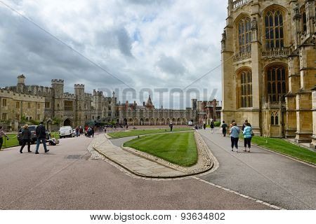 WINDSOR, ENGLAND - JUNE 11, 2015: Tourists walking through Windsor Castle, Berkshire, UK, grounds with the Round Tower in the Middle Ward, an official Royal residence on June 11, 2015