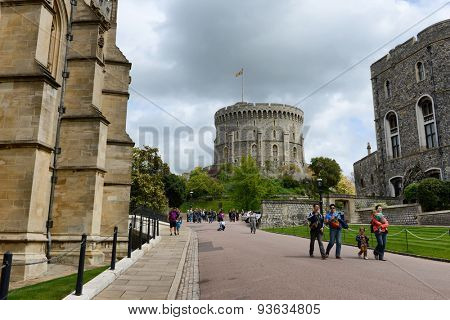 WINDSOR, ENGLAND - JUNE 11, 2015: Tourists walking through Windsor Castle, Berkshire, UK, grounds with the Round Tower in the Middle Ward visible in the background, on June 11, 2015