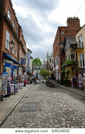 WINDSOR, ENGLAND - JUNE 11, 2015: Cobblestone Street Scenic Lined with Quaint Souvenir Shops, Historical Town of Windsor, Berkshire, England on June 11, 2015