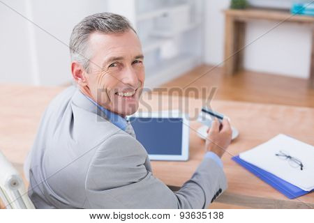 Smiling businessman holding tablet and credit card in his office