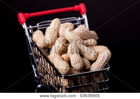 unshelled peanuts in the supermarket trolley on black background