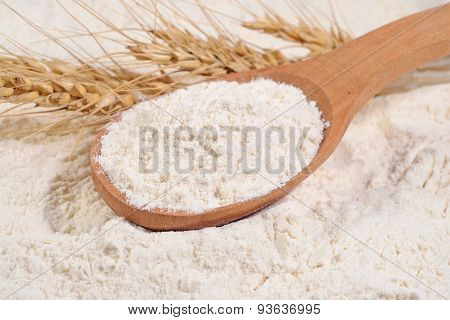 White Flour In A Wooden Spoon And Ears Of Wheat